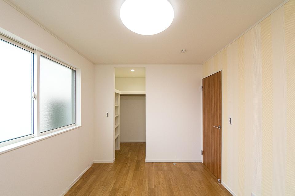扉をつけないオープンなウォークインクローゼットをしつらえた2階洋室。