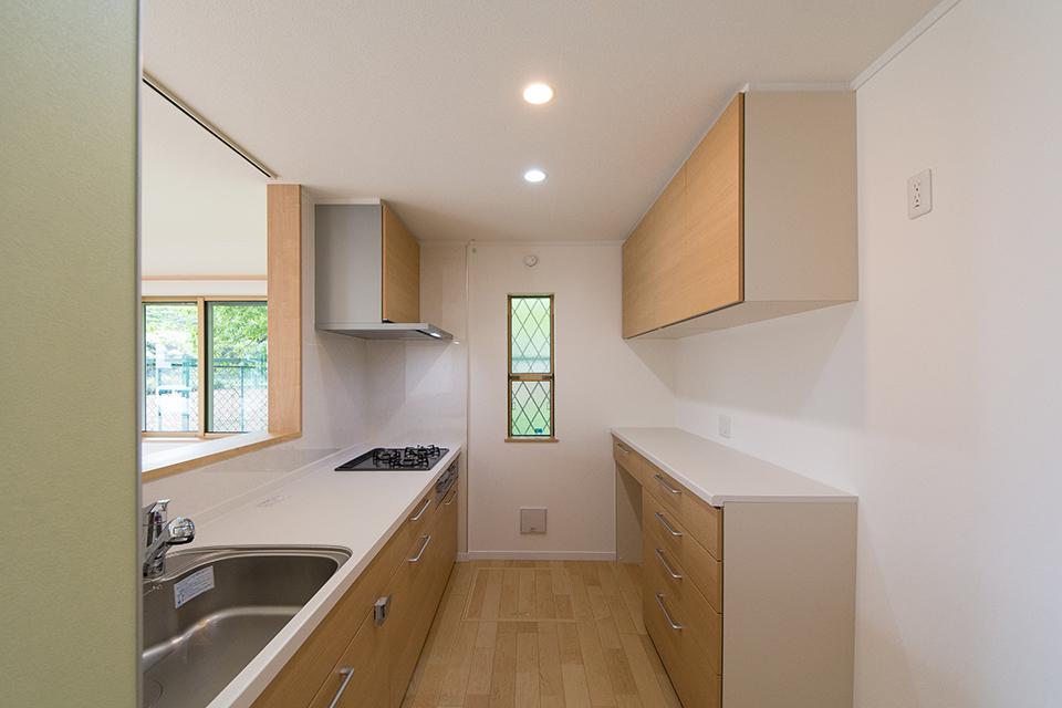 ブラウンのキッチン扉とカップボード。ナチュラルであたたかみのあるキッチンスペースに。