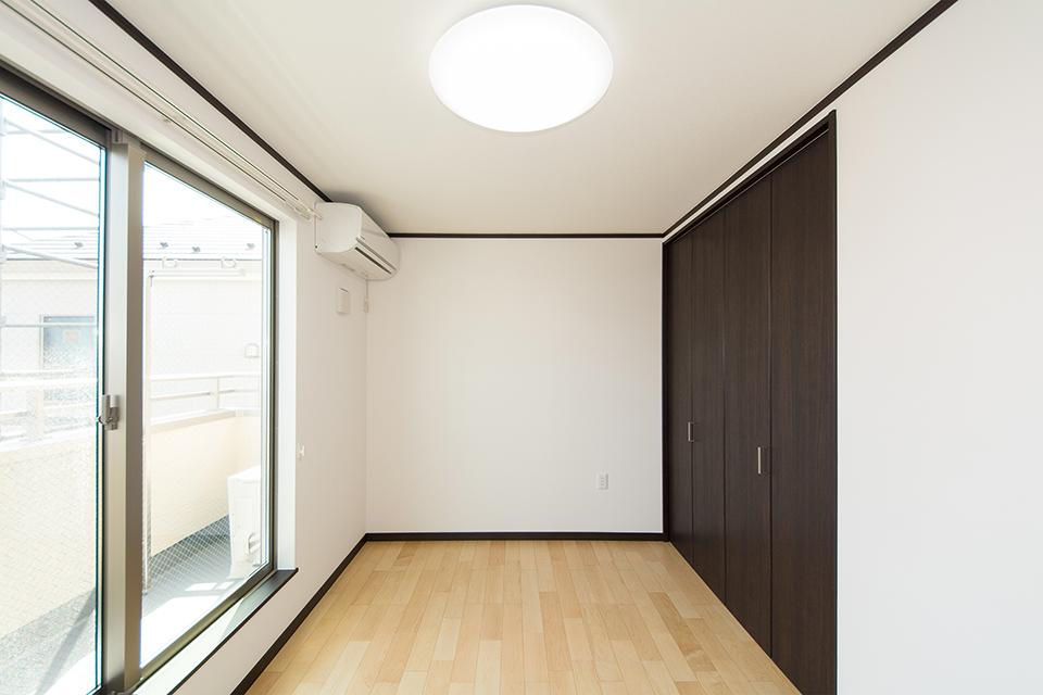 2階洋室。ダークブラウンの建具が空間を引き締めます。