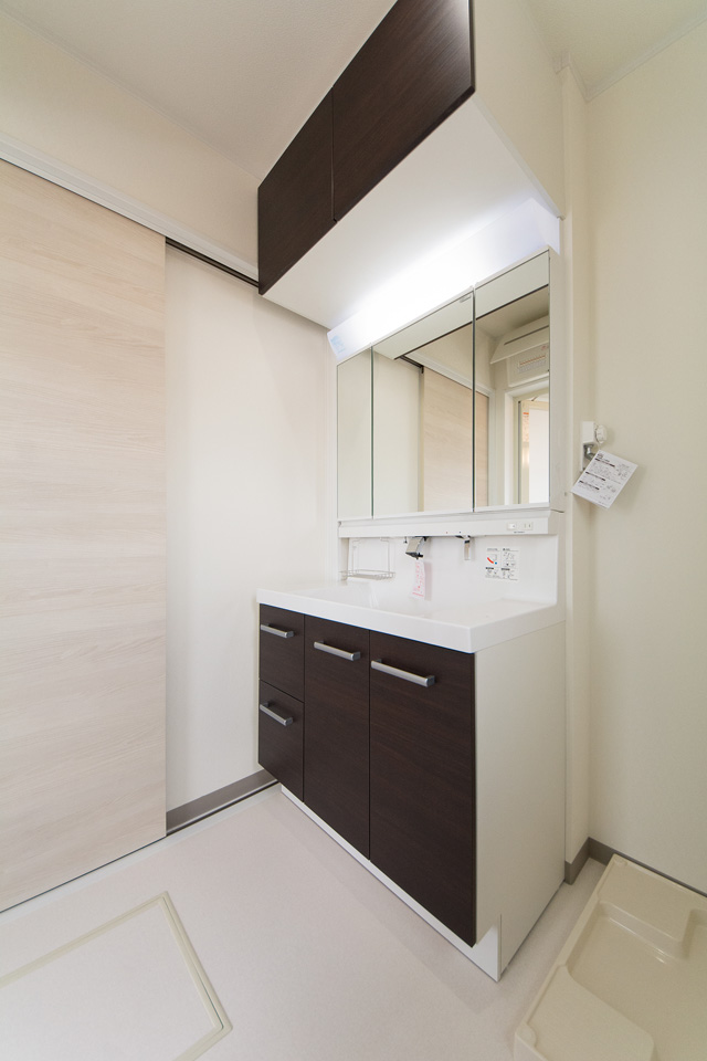 白を基調とした清潔感のあるサニタリールーム。ダークのブラウンの洗面化粧台が印象的。