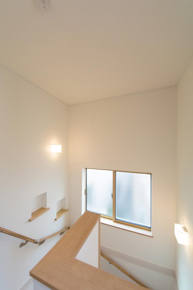 大きな窓をしつらえた、明るく開放感のある階段。おしゃれで便利なニッチカウンターを設置。