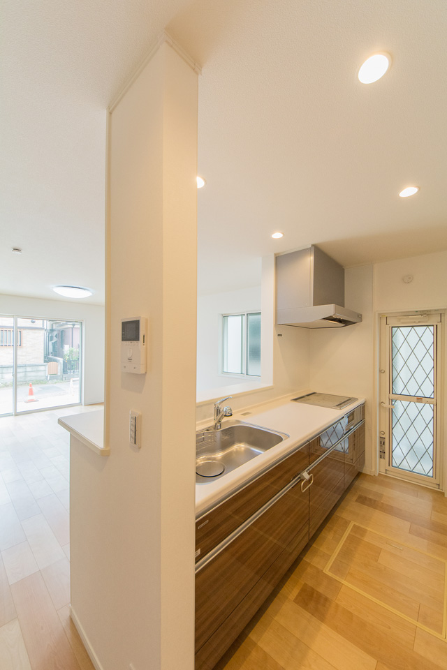 木のやさしい風合いでナチュラルな雰囲気のキッチン扉。白を基調とした清潔感のある空間に。