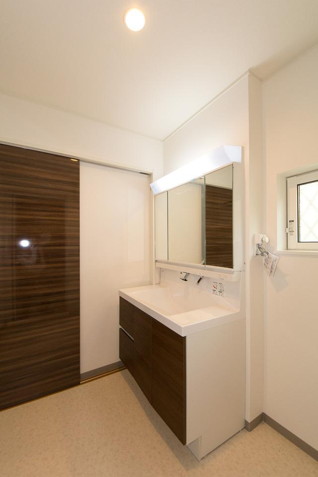 白を基調とした清潔感のあるサニタリールーム。ブラウンの洗面化粧台がナチュラルな雰囲気の空間を演出。
