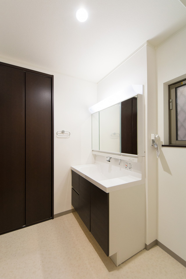 を基調とした清潔感のあるサニタリールーム。ダークのブラウンの洗面化粧台が印象的。