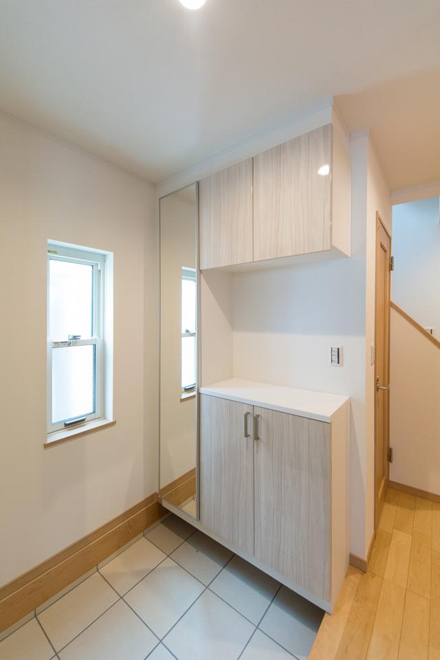 鏡面仕上げの収納扉と白のテラコッタ調タイルがナチュラルな雰囲気を演出。