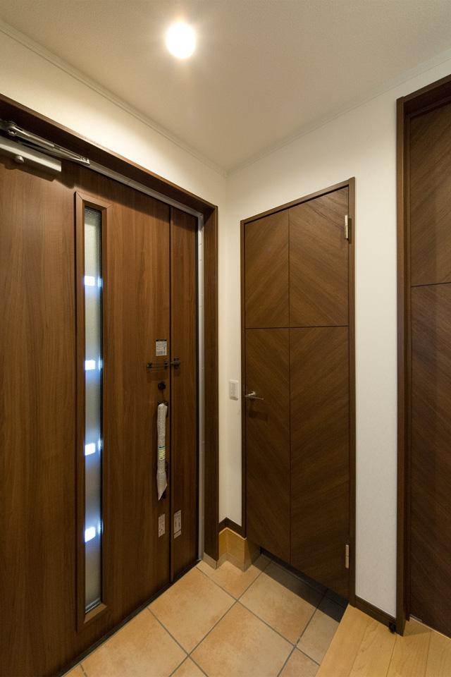 縦スリットから自然の光が差し込む明るい玄関。