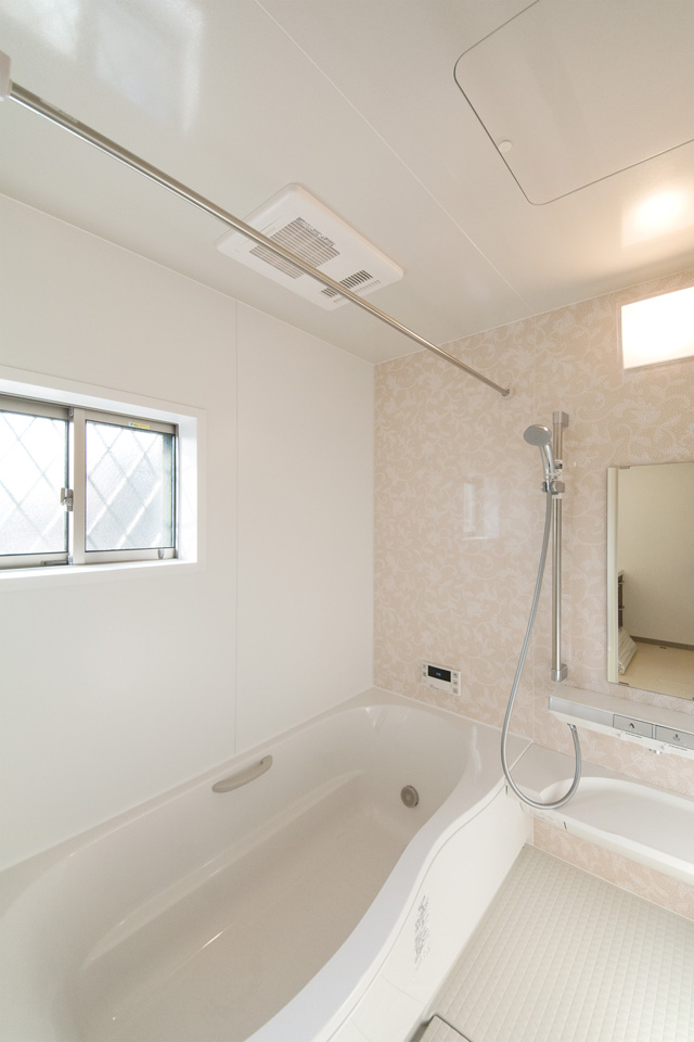 ライトピンクのアクセントパネルで爽やかな印象のバスルーム。