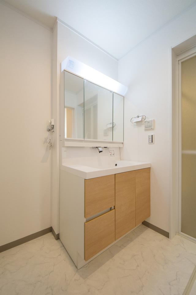 白を基調としたサニタリールーム。洗面化粧台のブラウンがあたたかみのある空間を演出。