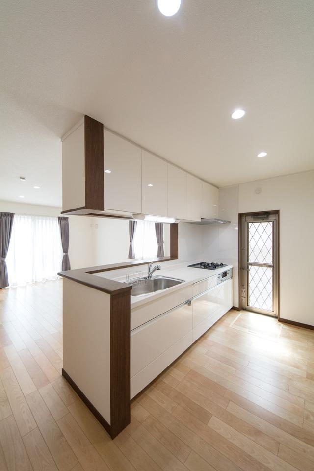 白を基調とした清潔感のあるキッチンスペース。ブラウンの化粧板がナチュラルな雰囲気をプラス。