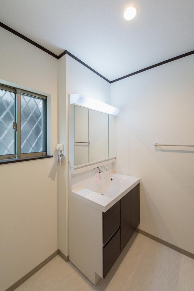 白を基調とした清潔感のあるサニタリールーム。ダークブラウンの洗面化粧台がエレガントな雰囲気に。