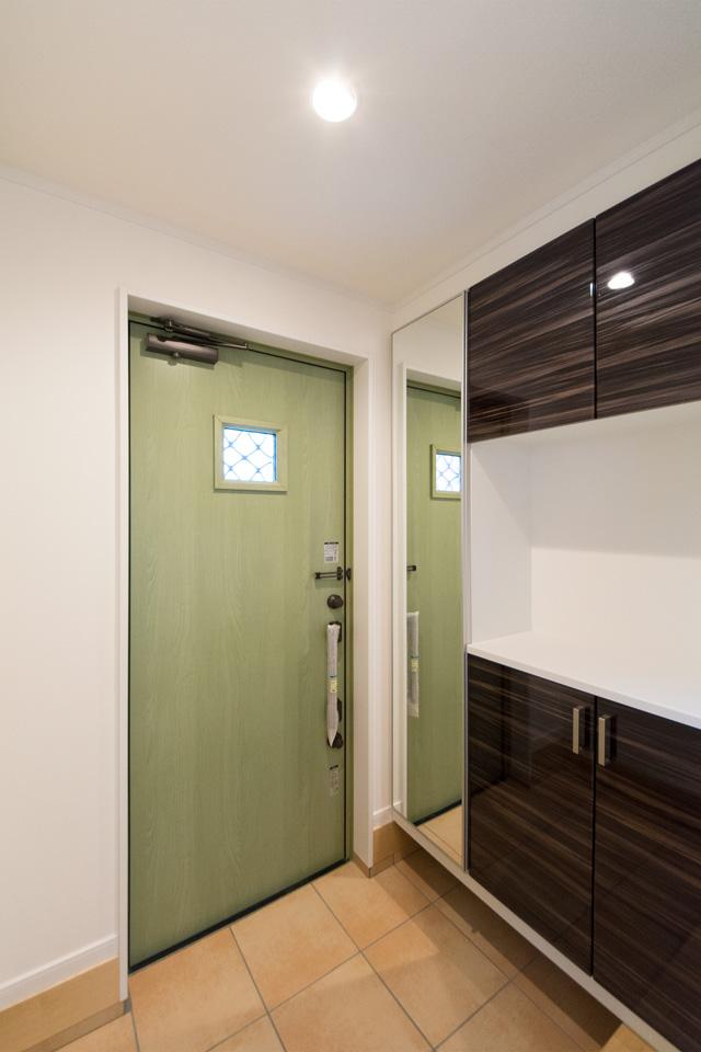 リーフグリーンの玄関ドアとベージュのタイルがナチュラルであたたかみのある空間を演出します。
