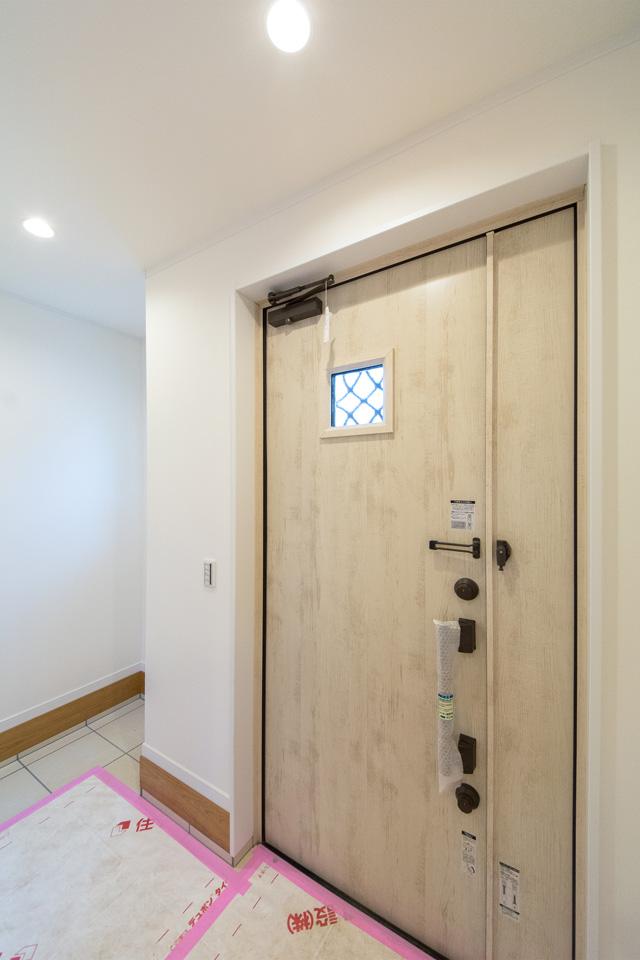 ナチュラルな雰囲気を演出するアイボリーの玄関ドア。