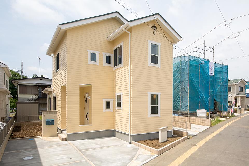 黄色の木目調外壁に白の窓モールをあしらったファサードデザイン。