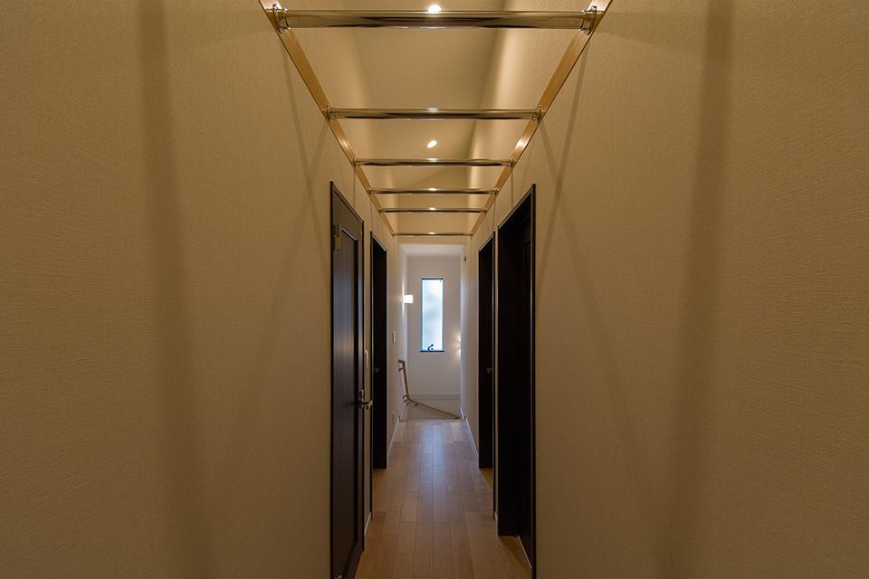 2階廊下。屋根の形に合わせて傾斜を持たせた勾配天井を設えました。空間が広がり開放的です。