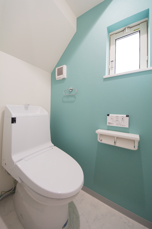 爽やかな印象を与えるターコイズブルーのアクセントクロスが印象的な1階トイレ。