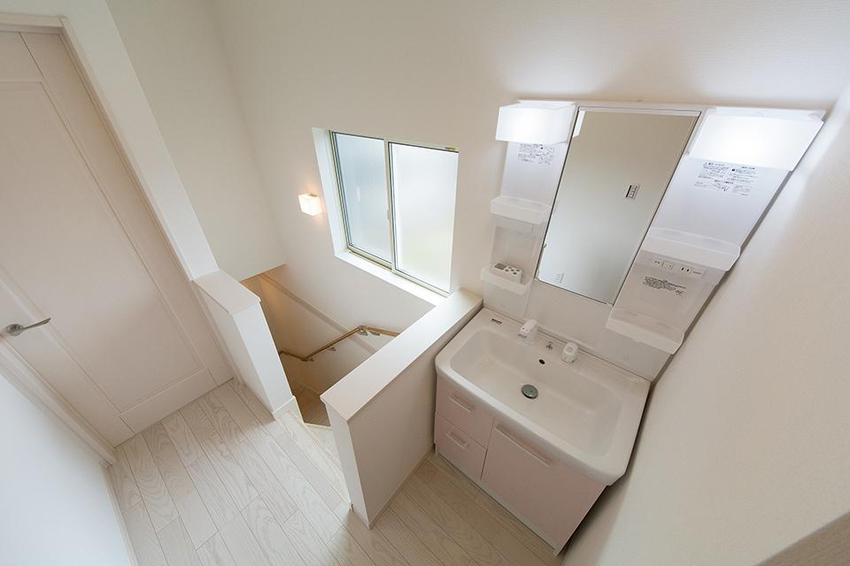 パステルピンクの扉が明るく爽やかな印象を与える2階洗面化粧台。