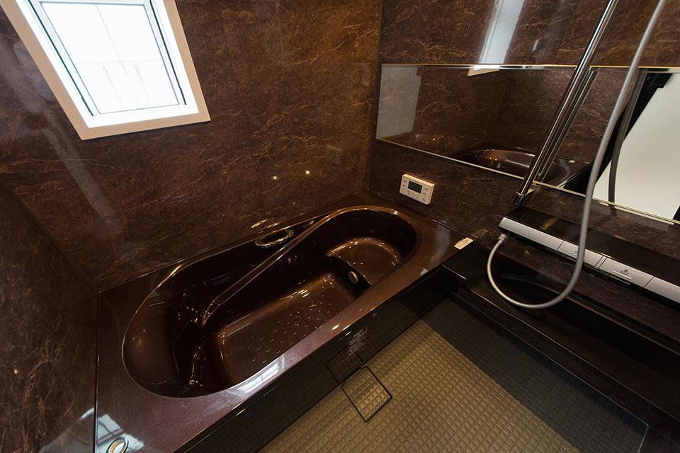 ゴールドブラウンの浴槽とシックなアクセントパネルで、エレガントな雰囲気で上質な空間に。
