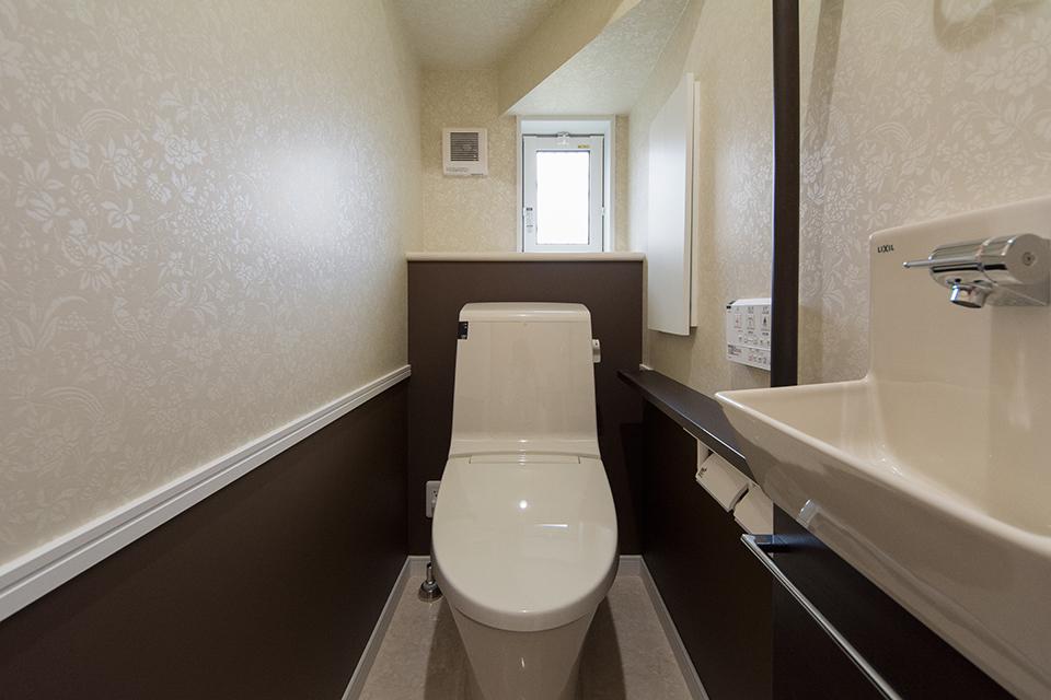 アクセントクロスを上下で貼り分けた、ナチュラルな雰囲気の1階トイレ