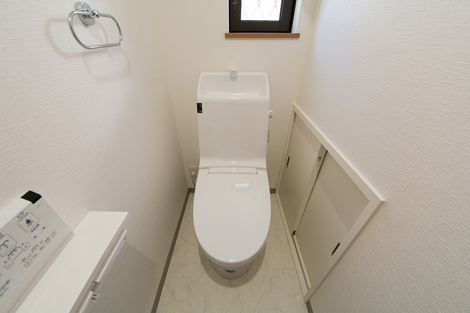 白を基調とした清潔感のある1階トイレ。 階段下のスペースを収納に。
