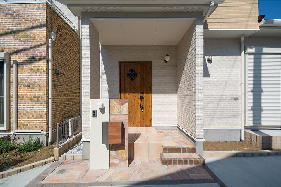 アイリッシュパインの玄関ドアと、ベージュのテラコッタ調タイルがナチュラルな雰囲気を演出。