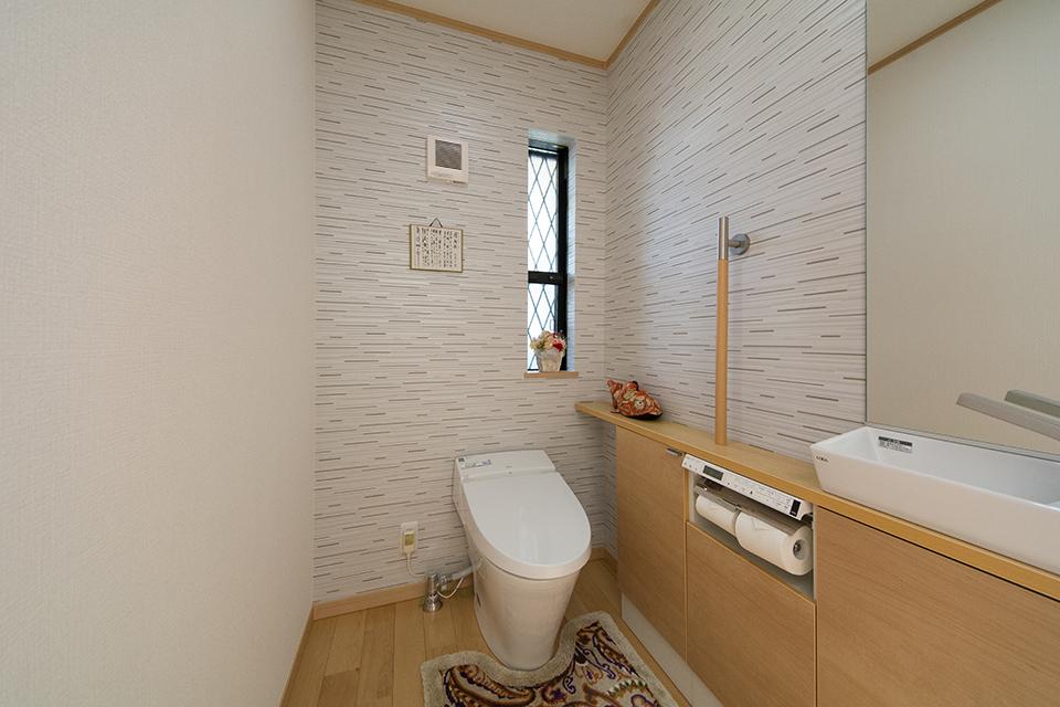 トイレ。白を基調にブラウンの建具がナチュラルな空間を演出。