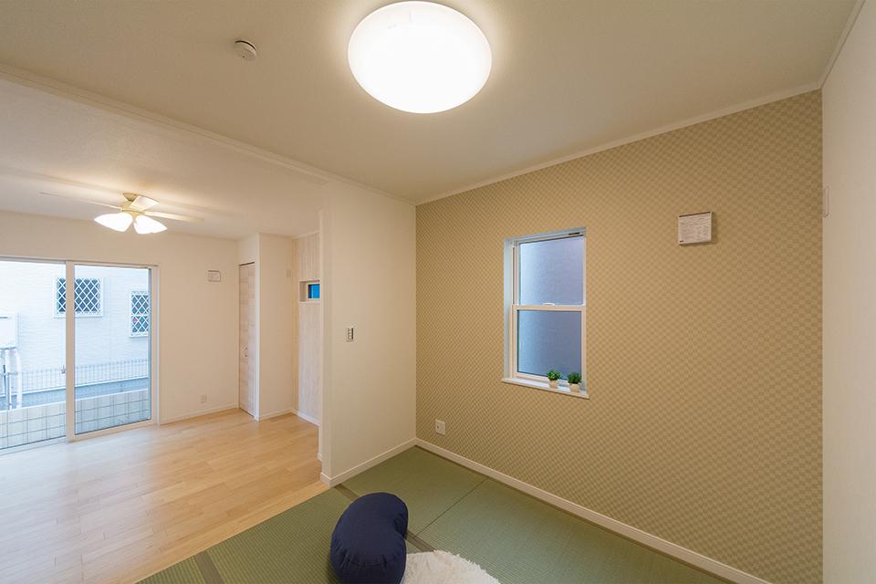 畳のさわやかなグリーンが空間を彩る小上がりになった畳敷きスペース。ブラウンのアクセントクロスが落ち着いた雰囲気を演出。