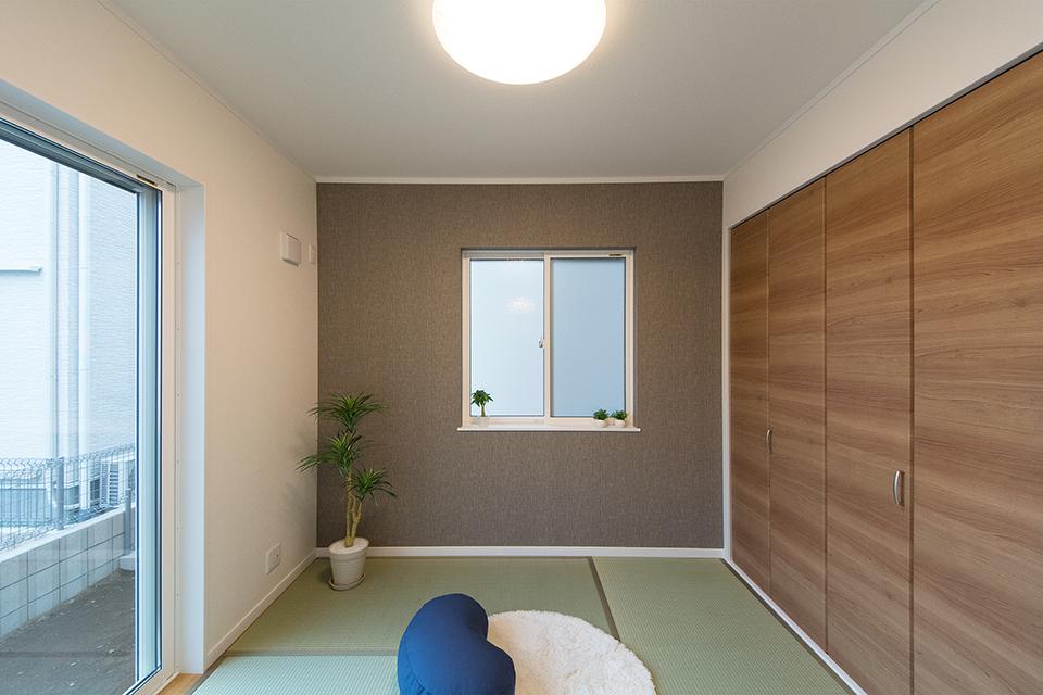 畳のさわやかなグリーンが空間を彩る1階畳敷きスペース。ブラウンのアクセントクロスが落ち着いた雰囲気を演出。