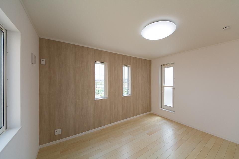 ウッド調のナチュラルなアクセントクロスをあしらった2階主寝室。