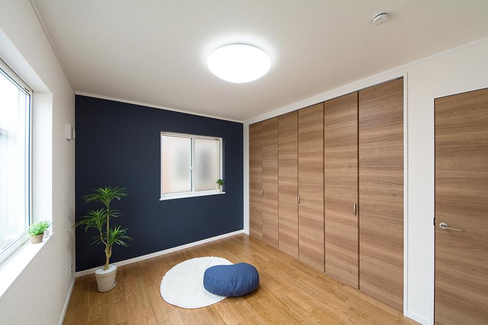 ネイビーのアクセントクロスが爽やかな印象の空間を演出する2階洋室。