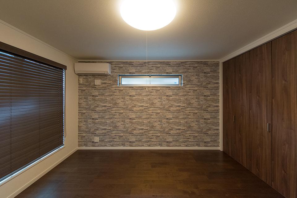 シックな配色で落ち着いた雰囲気の2階洋室。石目調のアクセントクロスが印象的です。