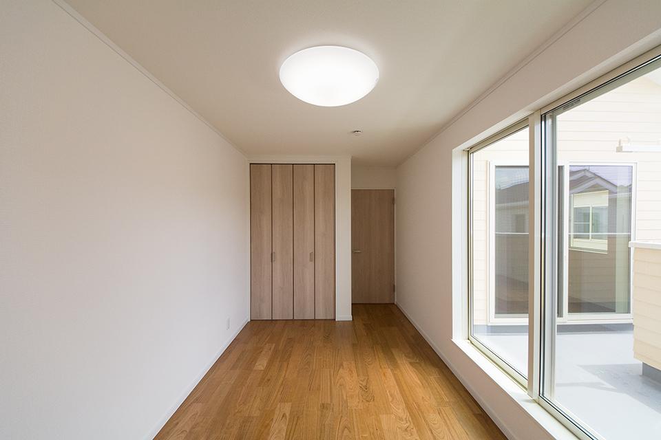 2階洋室。リビング同様ブラックチェリーのフローリングとオークの建具がナチュラルな空間を演出。