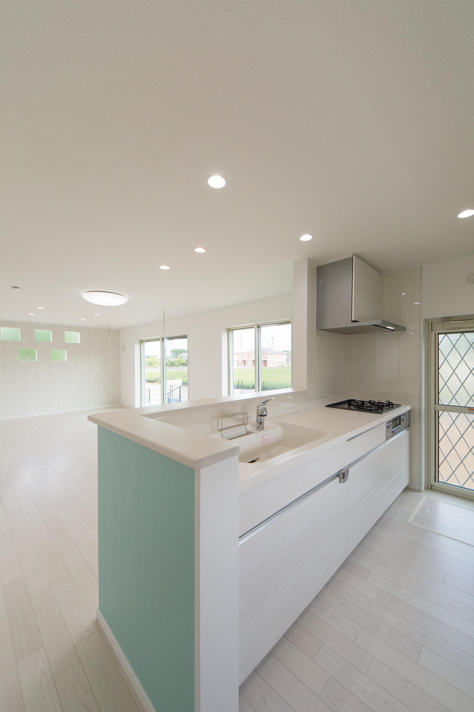 白を基調とした清潔感のあるキッチンスペース。カウンター周囲のアクセントクロスが爽やかな印象をプラス。