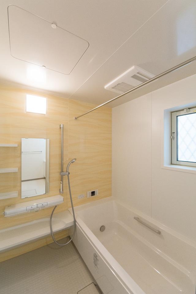 明るいオレンジのアクセントパネルをあしらった、清潔感のあるバスルーム。