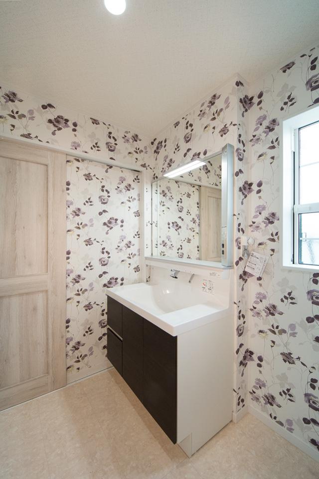 白を基調とした清潔感のあるサニタリールーム。花柄のアクセントクロスが空間を彩ります。