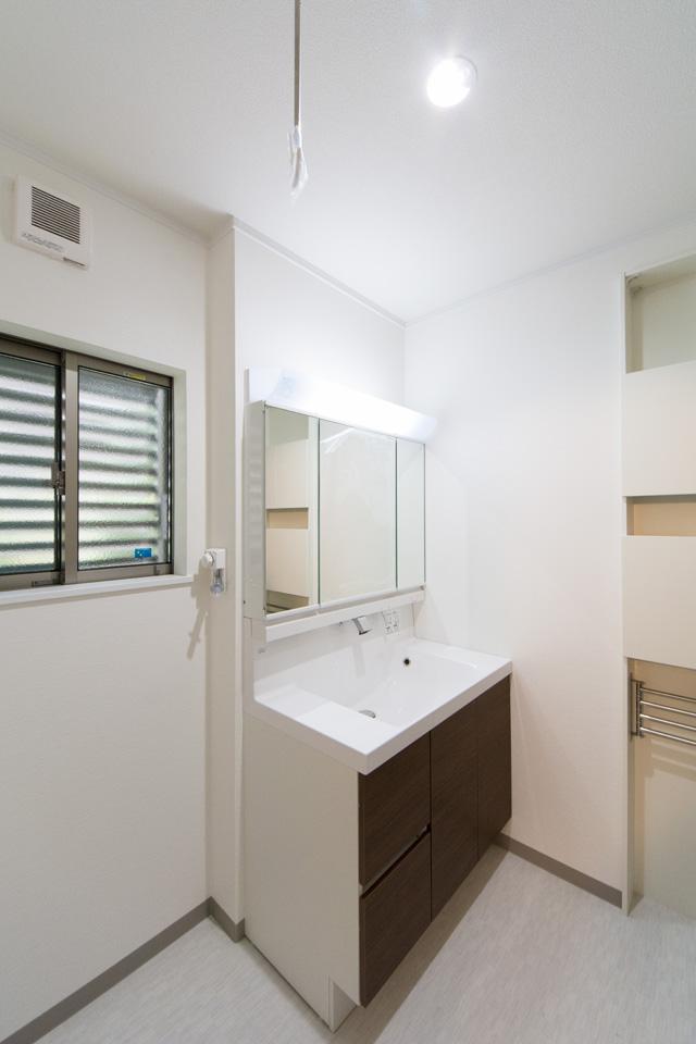 ブラウンの洗面化粧台がナチュラルな雰囲気の空間を演出する1階サニタリールーム。