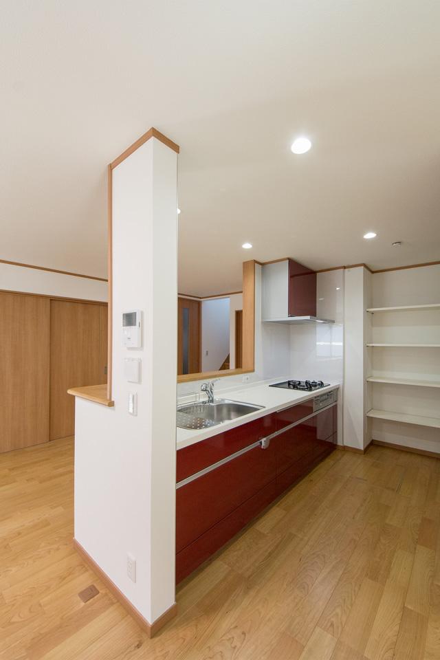 ディープレッドのキッチン扉がスペースを彩ります。奥には収納に便利なパントリーを設えました。