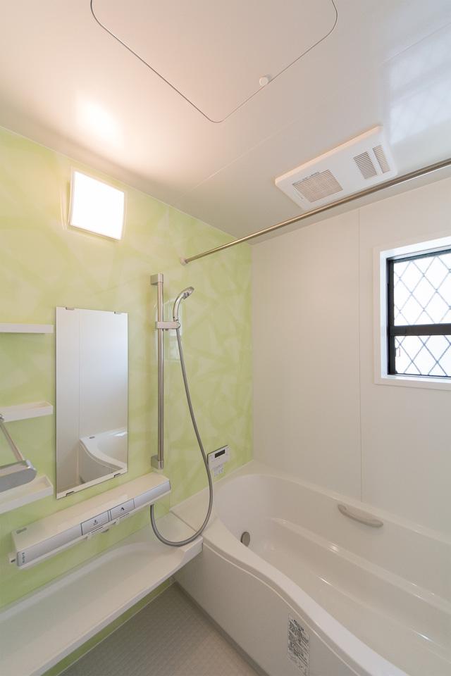 ミントグリーンのアクセントパネルで、爽やかな空間のバスルーム。
