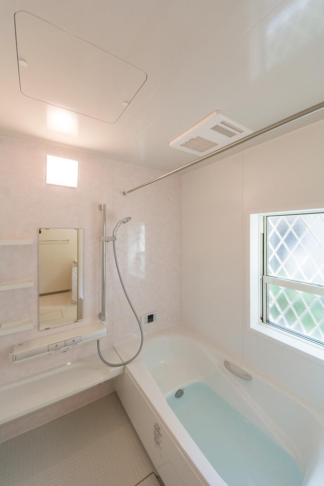 バスルーム。フラワーシーン柄のアクセントパネルが爽やかな空間を演出。