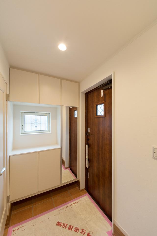 ナチュラルな雰囲気を演出するチェリーの玄関ドアと赤のテラコッタ調タイル。
