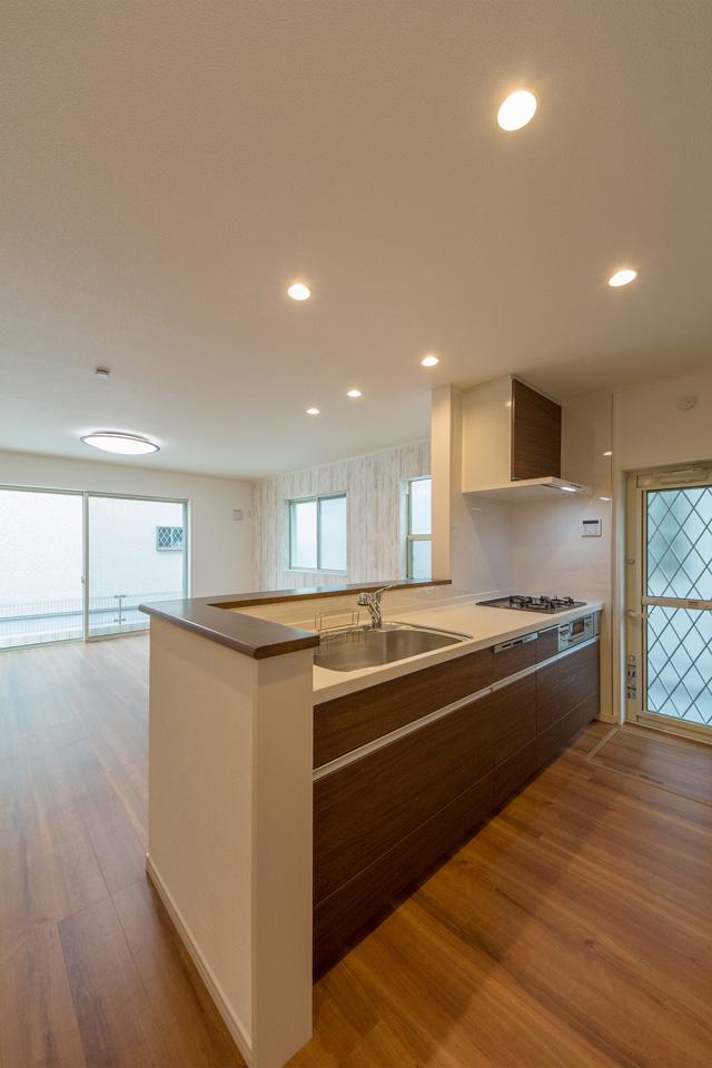 白を基調とした清潔感あるキッチン。ブラウンのキッチン扉がナチュラルな雰囲気を演出。
