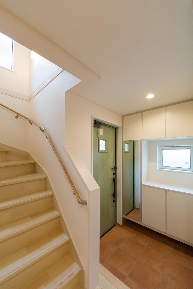リーフグリーンの玄関ドアとレッドのタイルがナチュラルで温かみのある空間を演出します。
