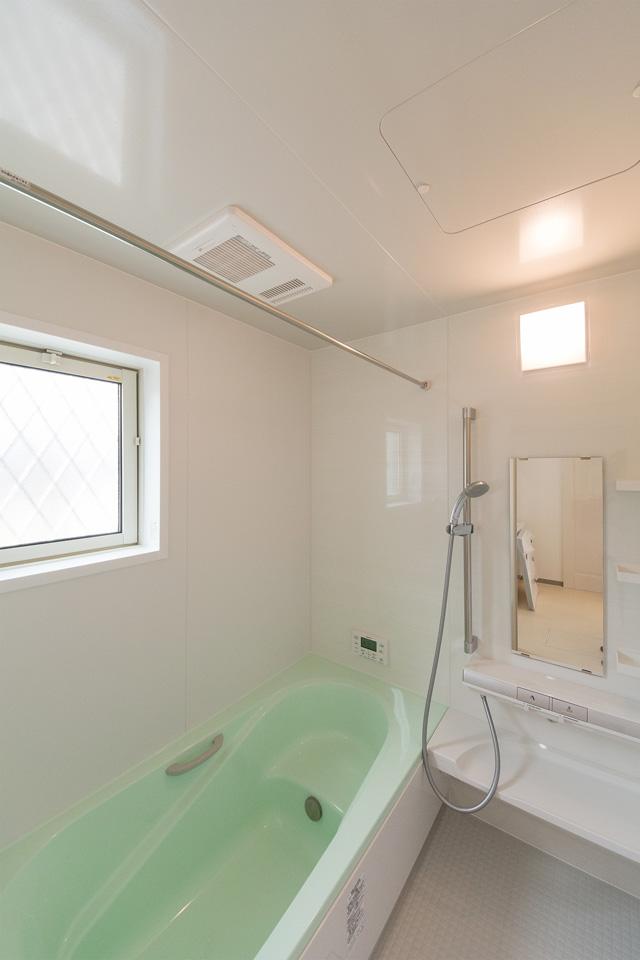 白を基調とした室内に、グリーンの浴槽がひときわ印象的なバスルーム。