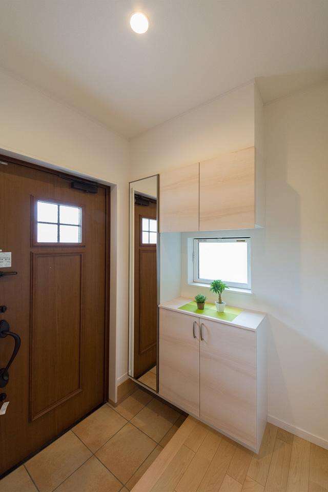 キャラメルチークの玄関扉とベージュのテラコッタ調タイルがナチュラルな雰囲気を演出。