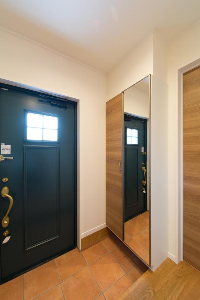 レッドのテラコッタ調タイルとグリーンの玄関ドアがエントランスを彩ります。
