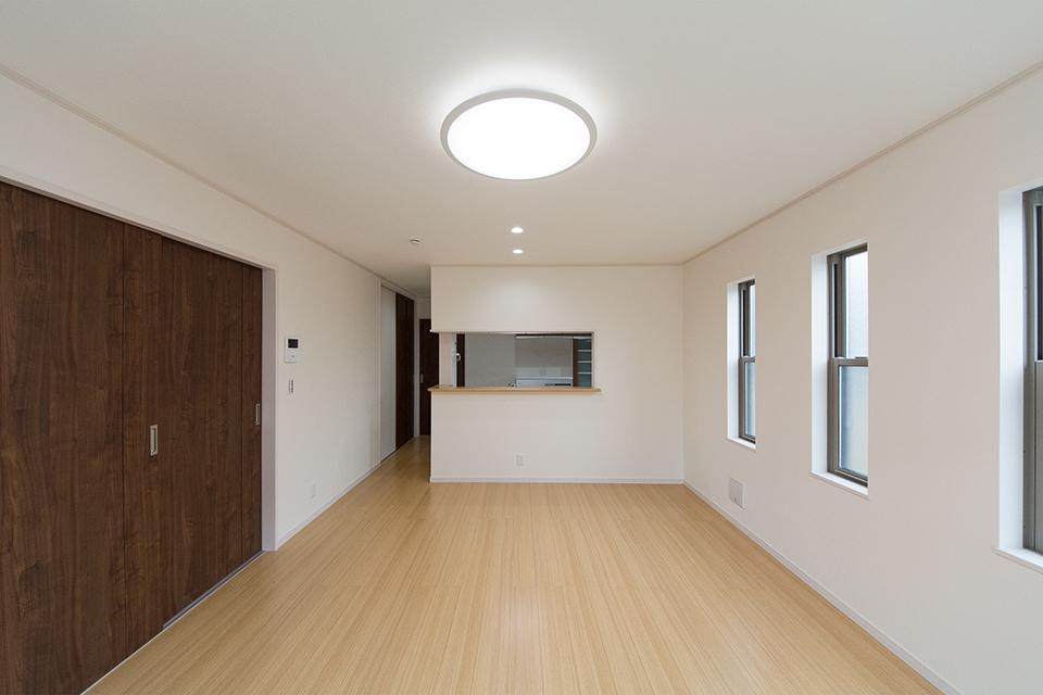 穏やかな色合いのフローリングとダークブラウンの建具がナチュラルな空間を演出。