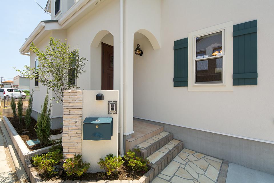 白の塗り壁にグリーンのよろい戸風窓飾りをあしらった、雰囲気のあるファサードデザイン。
