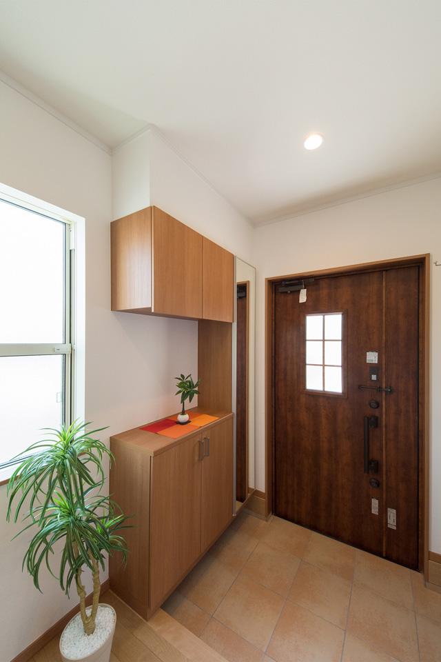 ハンドダウンチェリーの玄関ドアとベージュのテラコッタ調タイルが自然な風合いで穏やかな空間を演出。