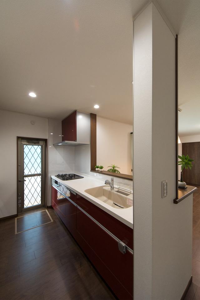 白を基調とした清潔感あるキッチン。ディープレッドのキッチン扉がエレガントな雰囲気を演出。