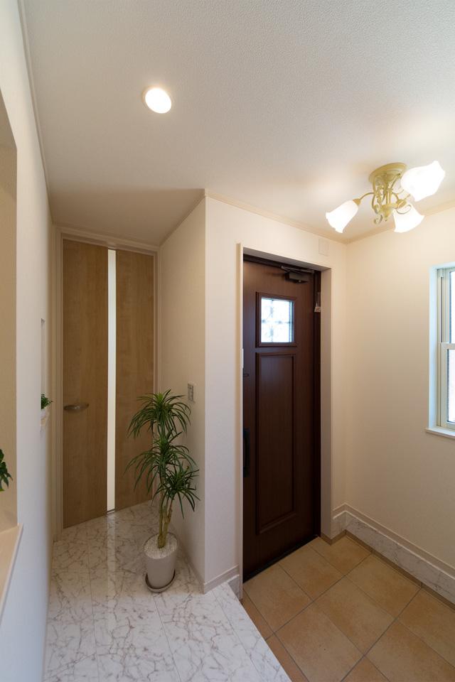 ナチュラルな雰囲気を演出するローストマホガニーの玄関ドアとベージュのテラコッタ調タイル。