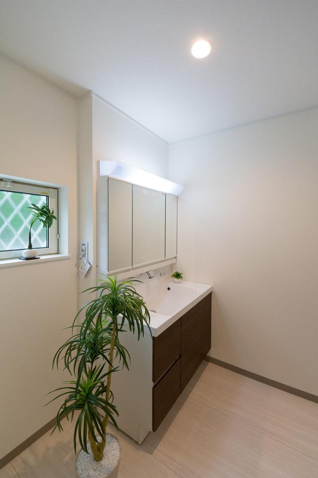 白を基調とした清潔感のあるサニタリールーム。モカ色の洗面化粧台がナチュラルな印象を与えます。